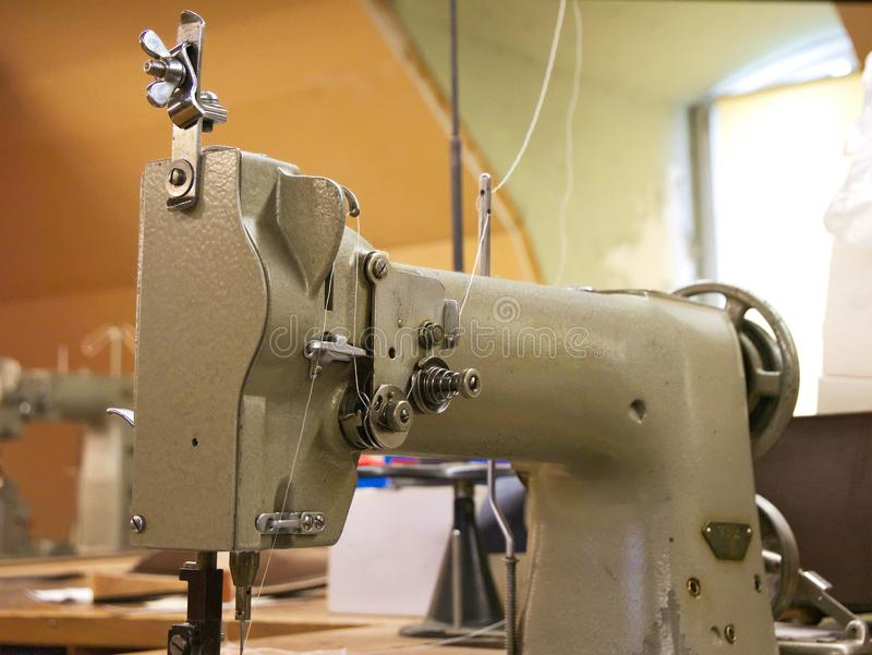 Old industrial factory sewing machine in close up royalty free stock photography