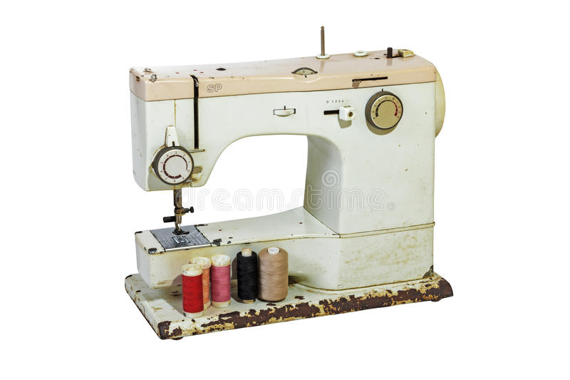 Old Rusty Sewing Machine with Colored Cottons. Old rusty vintage sewing machine with cotton reels, grungy scissors and tape measure on white background stock image