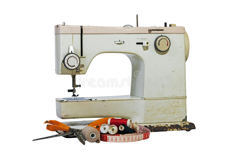 Old Rusty Vintage Sewing Machine with Cotton and Scissors. Old rusty vintage sewing machine with cotton reels, grungy scissors and tape measure on white stock photos