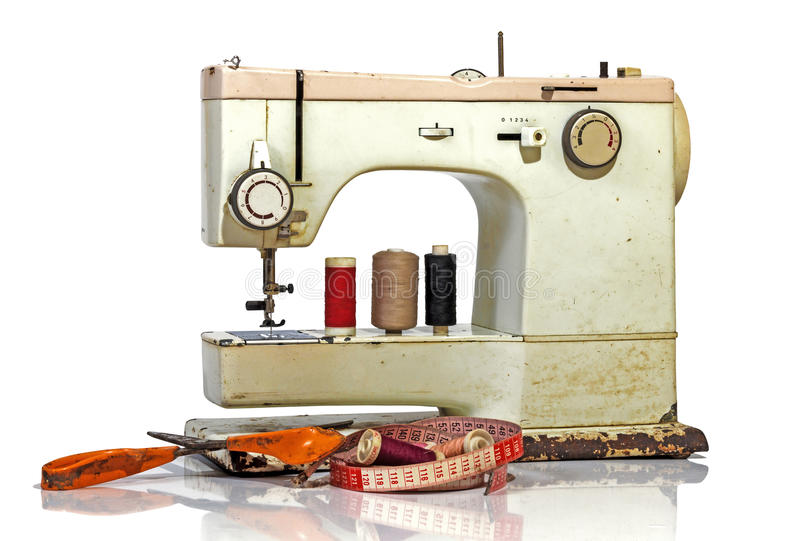 Old Rusty Vintage Sewing Machine with Scissors and Tape Measure. Old rusty vintage sewing machine with colored cotton reels, scissors tape measure and old royalty free stock photography