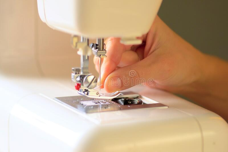 Preparing the sewing machine for work. Close up view. Preparing the sewing machine for work. Seamstress tucks thread into the eye of a needle. Installs the royalty free stock photos