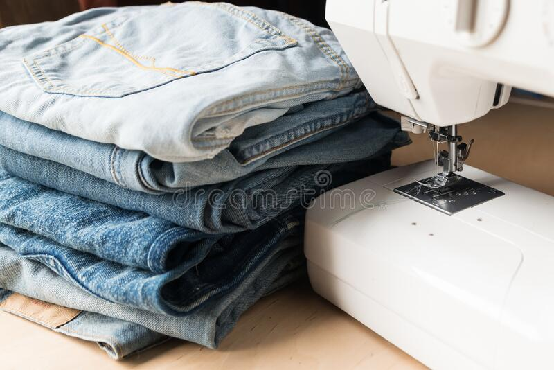 a stack of old torn jeans and a sewing machine on a wooden table stock photography